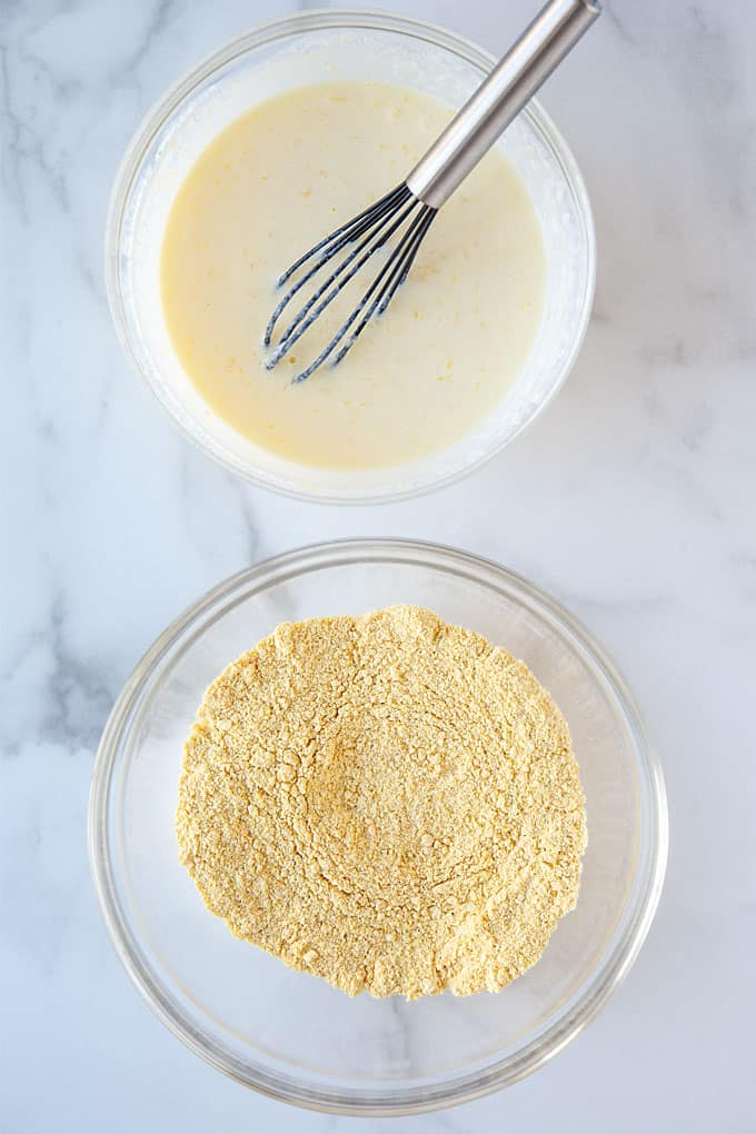 Overhead view of a bowl of wet ingredients and a bowl of dry ingredients for cornbread