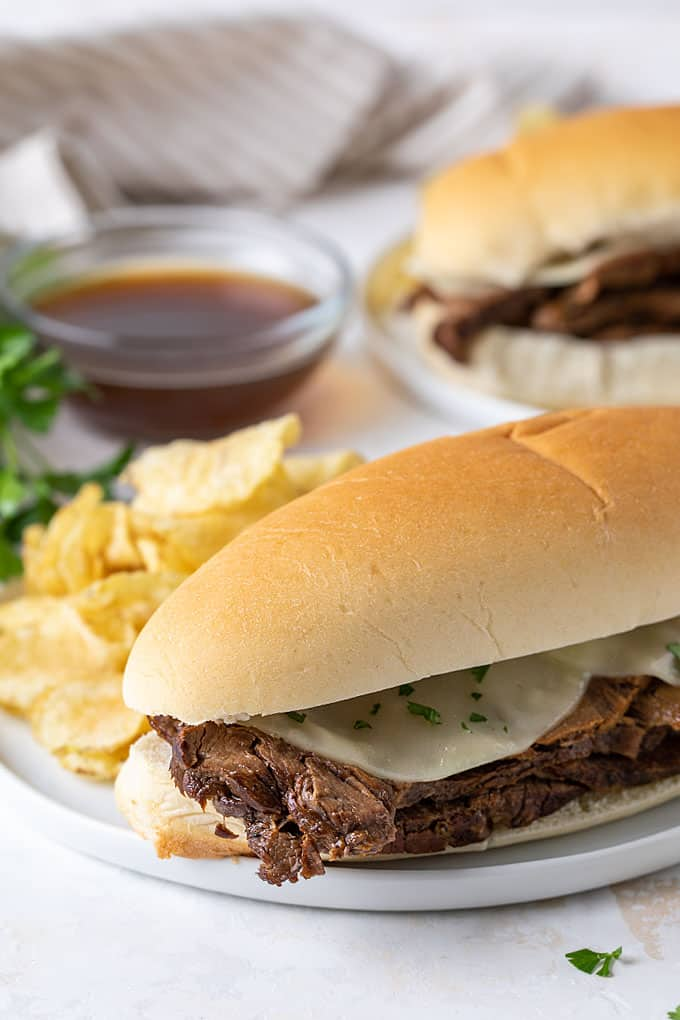 A French dip sandwich on a white plate with potato chips and a small bowl of au jus