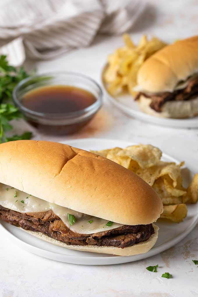 A French dip sandwich on a round white plate with potato chips. A bowl of au jus is in the background.