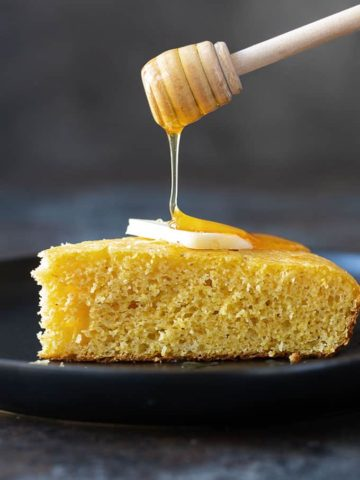 A slice of cornbread topped with a pat of butter on a black plate with a honey dipper pouring honey on top
