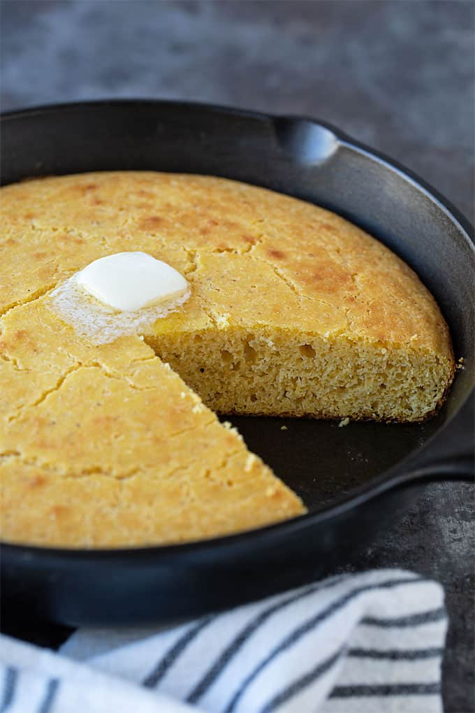 Cornbread in a cast iron skillet with a slice removed and a pat of melting butter on top