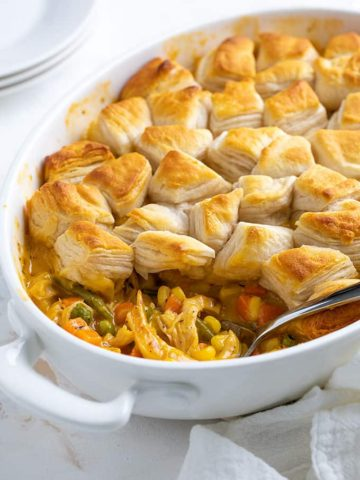 Chicken pot pie topped with canned biscuits in an oval white dish with a serving spoon.