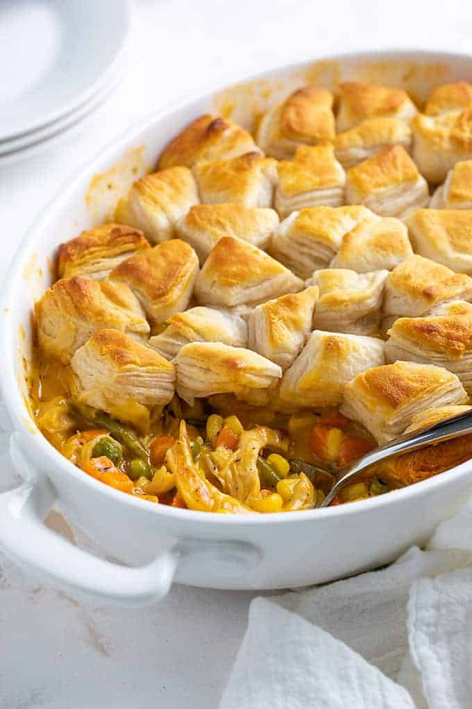 Chicken pot pie topped with canned biscuits in a baking dish with a spoon.