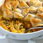 Chicken pot pie in a white baking dish with a serving spoon.