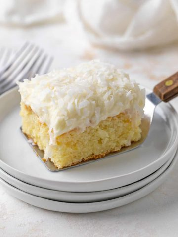 A slice of coconut cake being placed on a white plate with a server.