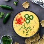 Overhead view of queso dip in a black bowl topped with cilantro, tomatoes and sliced jalapeno.