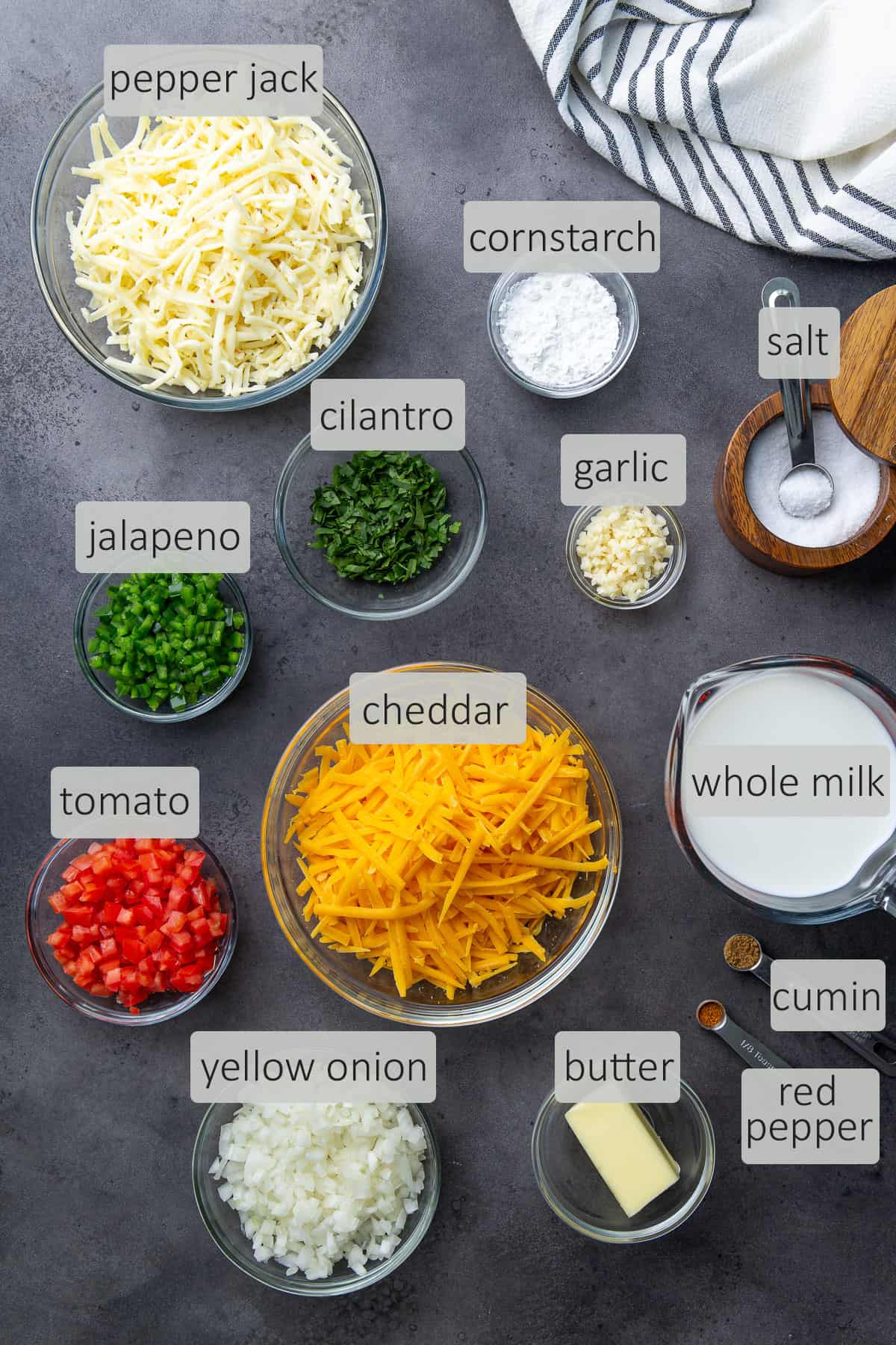 Overhead view of queso ingredients that are labeled on a dark gray background.