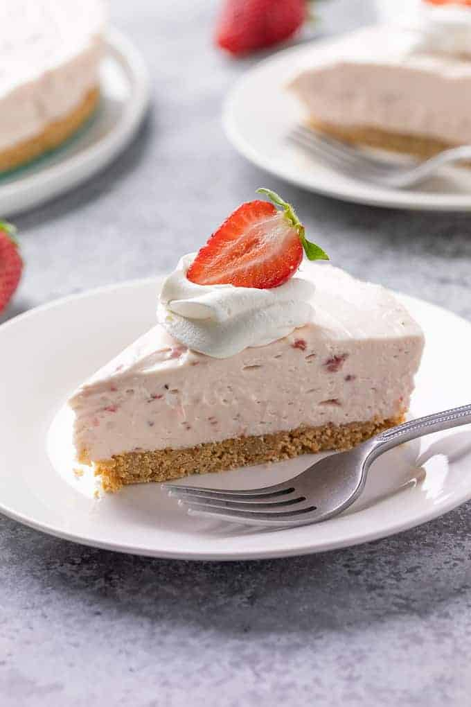 A slice of cheesecake on a white plate with a fork.