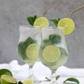 Front view of two mojitos on a white surface and a gray background.