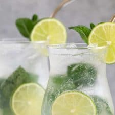 Front closeup view of two mojito cocktails with stainless straws.