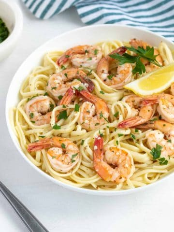 Shrimp scampi with pasta in a white bowl garnished with parsley and a lemon wedge.
