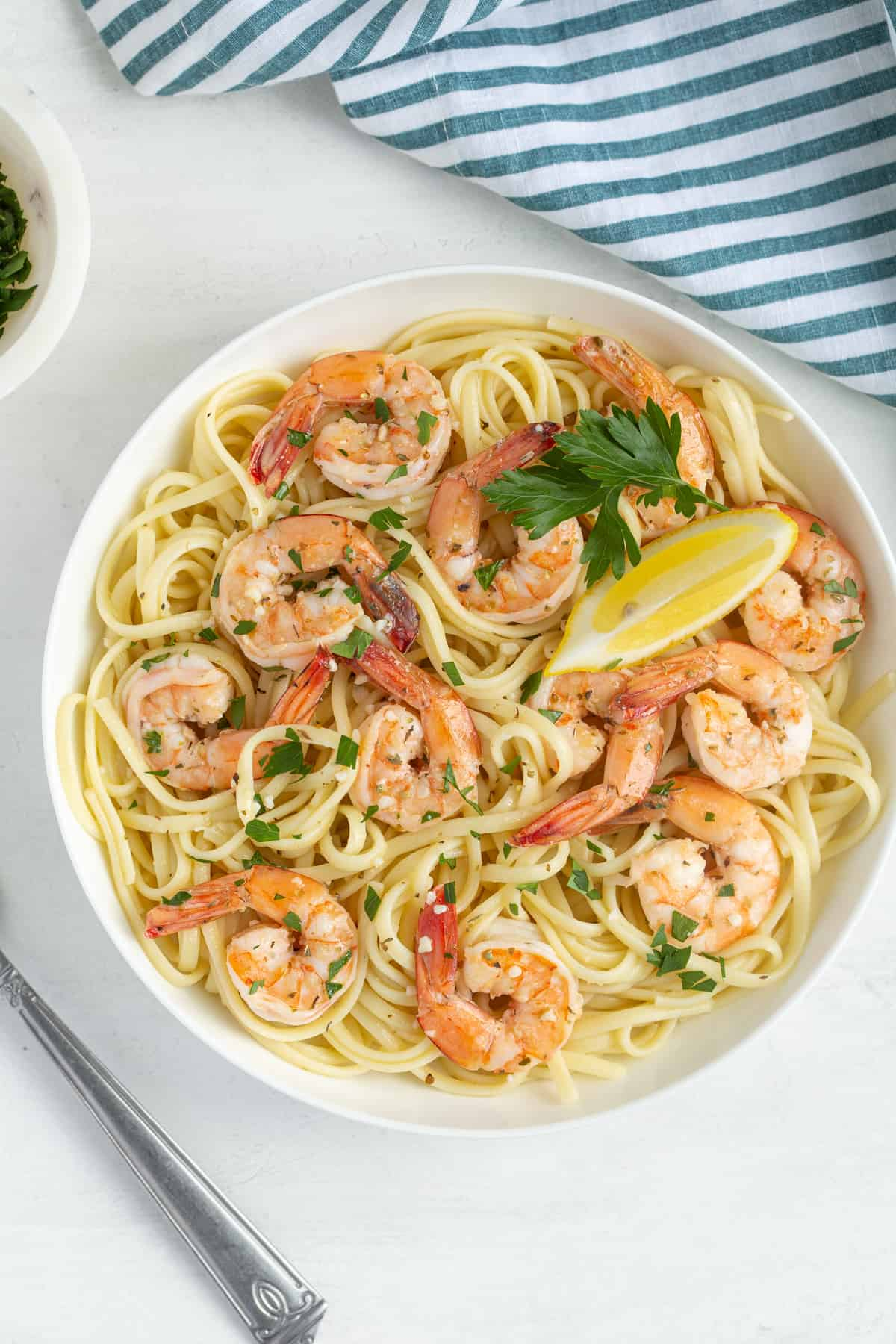 Overhead view of shrimp scampi pasta in a white bowl by a striped towel and a fork.