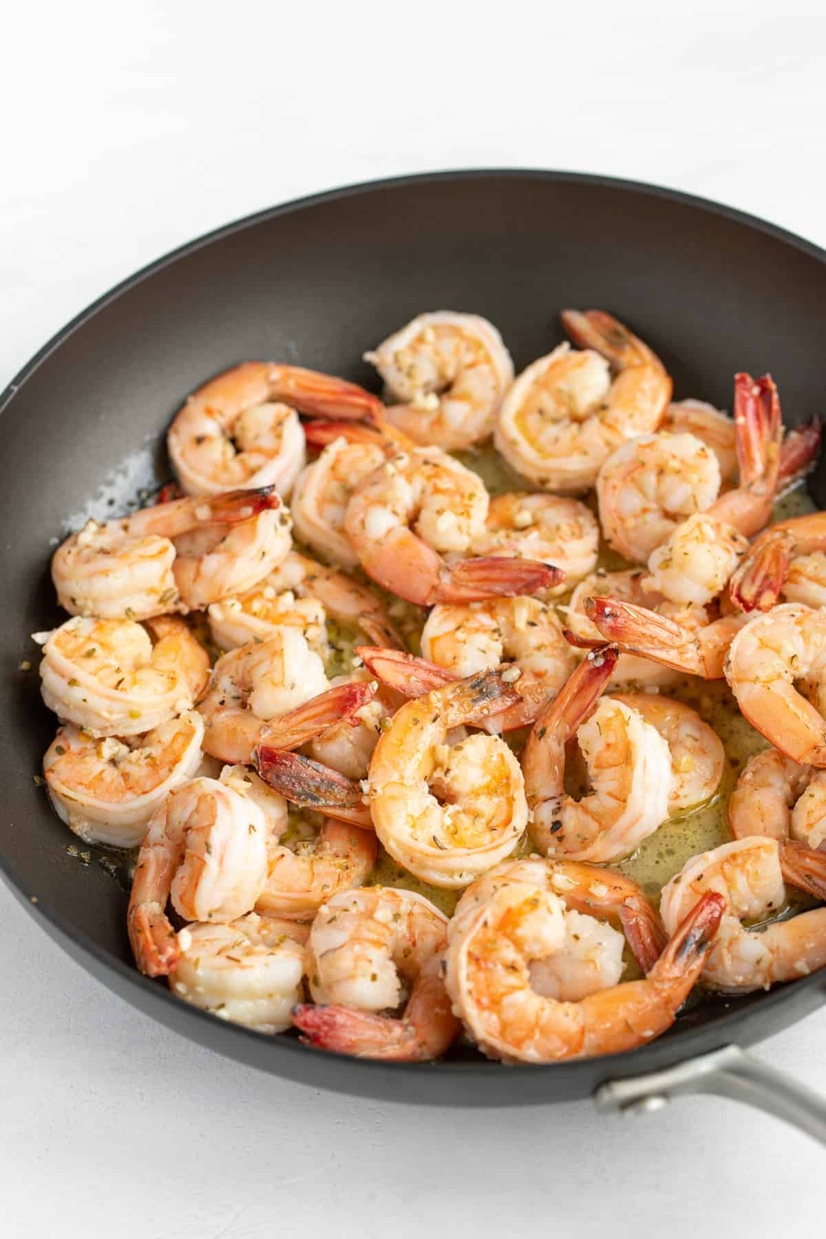 Cooked shrimp in melted butter and olive oil in a skillet on a white surface.