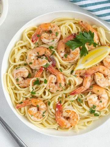 Overhead view of shrimp and pasta in a white bowl on a white surface.