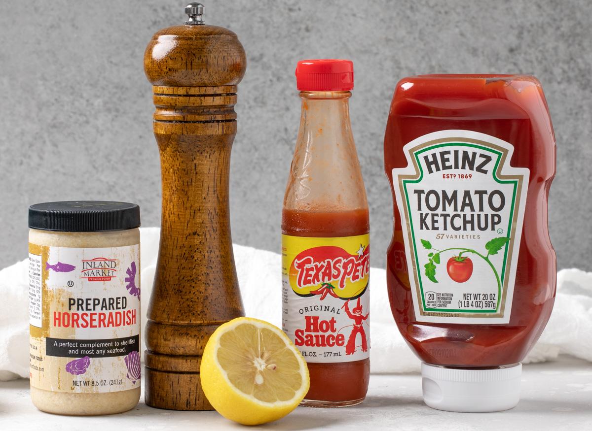A jar of horseradish, a pepper mill, hot sauce, ketchup and a lemon.