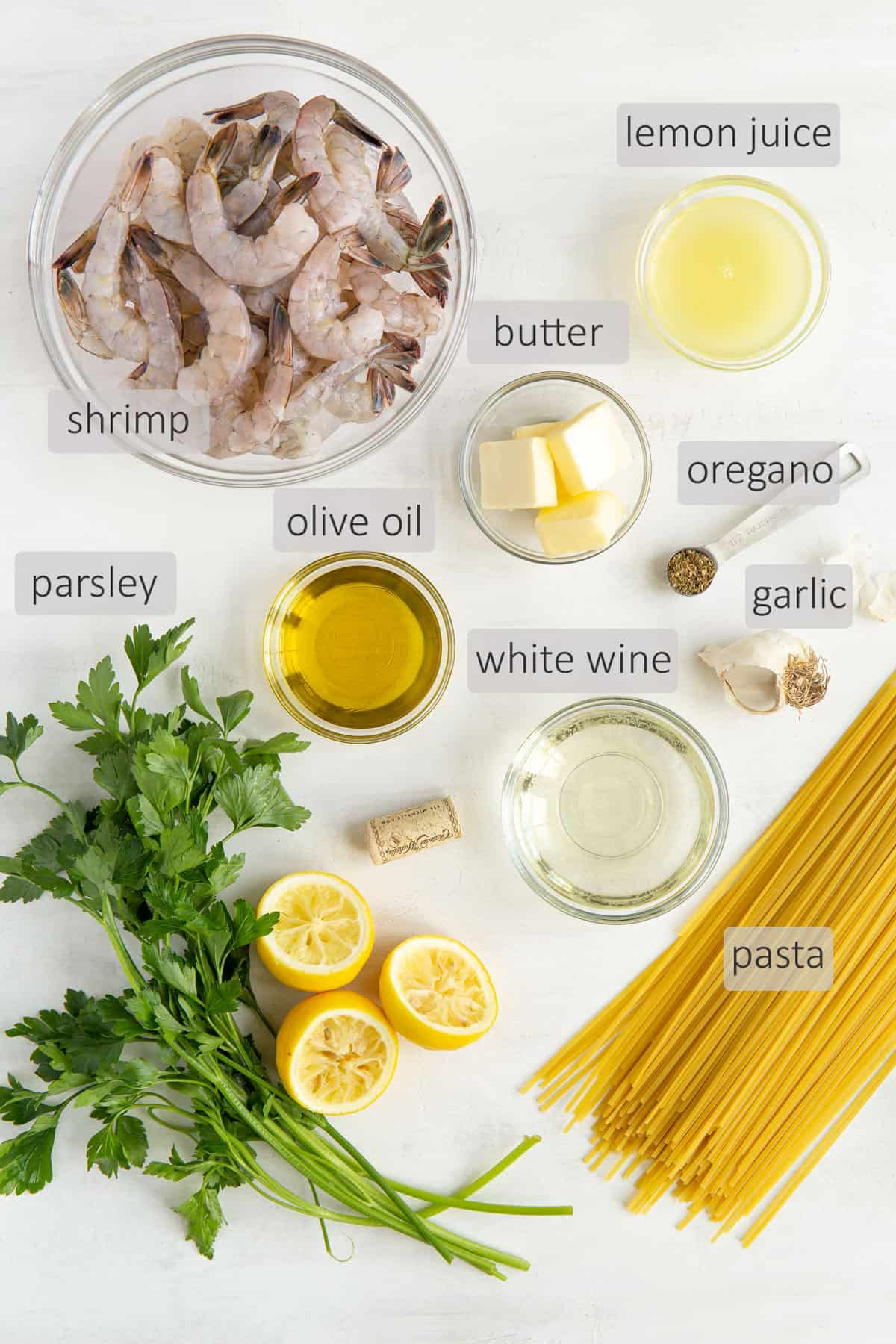 Overhead view of ingredients for shrimp scampi pasta on a white surface.