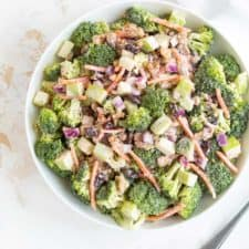 Overhead view of broccoli salad in a white bowl beside a spoon.