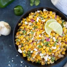 Overhead view of corn salad in a black bowl on a blue surface.