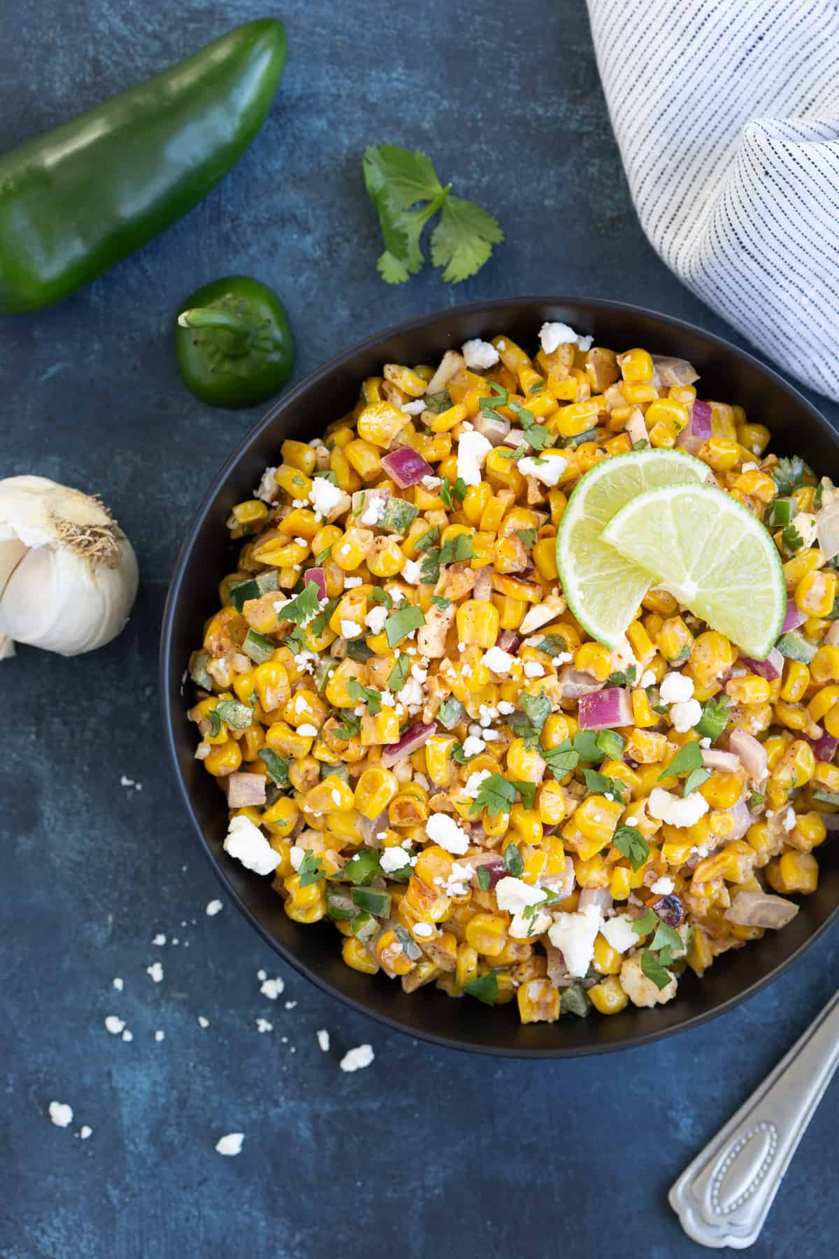 Overhead view of Mexican corn salad in a black bowl on a blue surface.