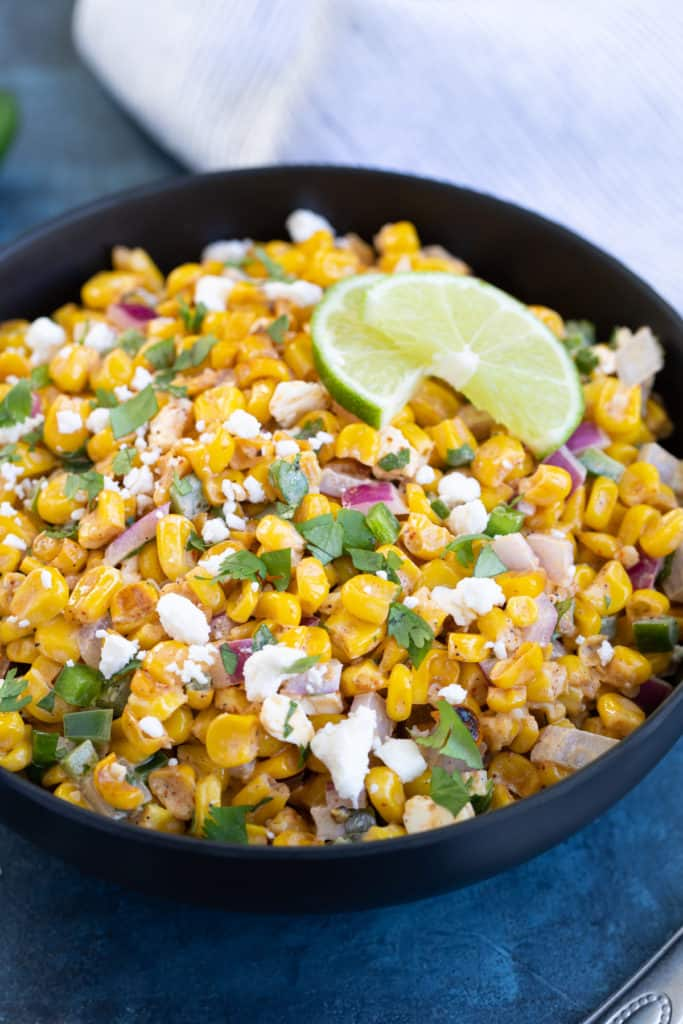 Closeup of a black bowl of corn salad topped with chopped fresh cilantro.