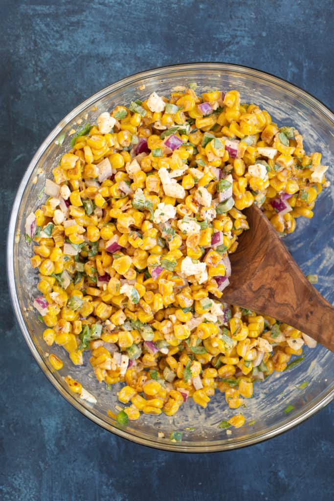 Overhead view of corn salad in a glass bowl with a wooden spoon.