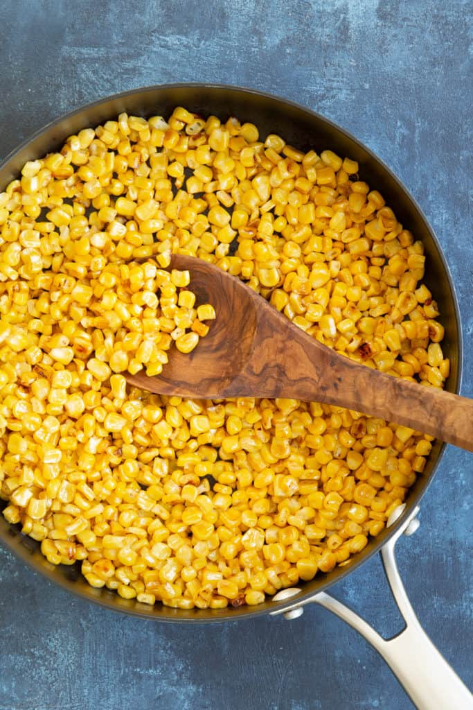 Overhead view of cooked yellow corn kernels in a skillet.