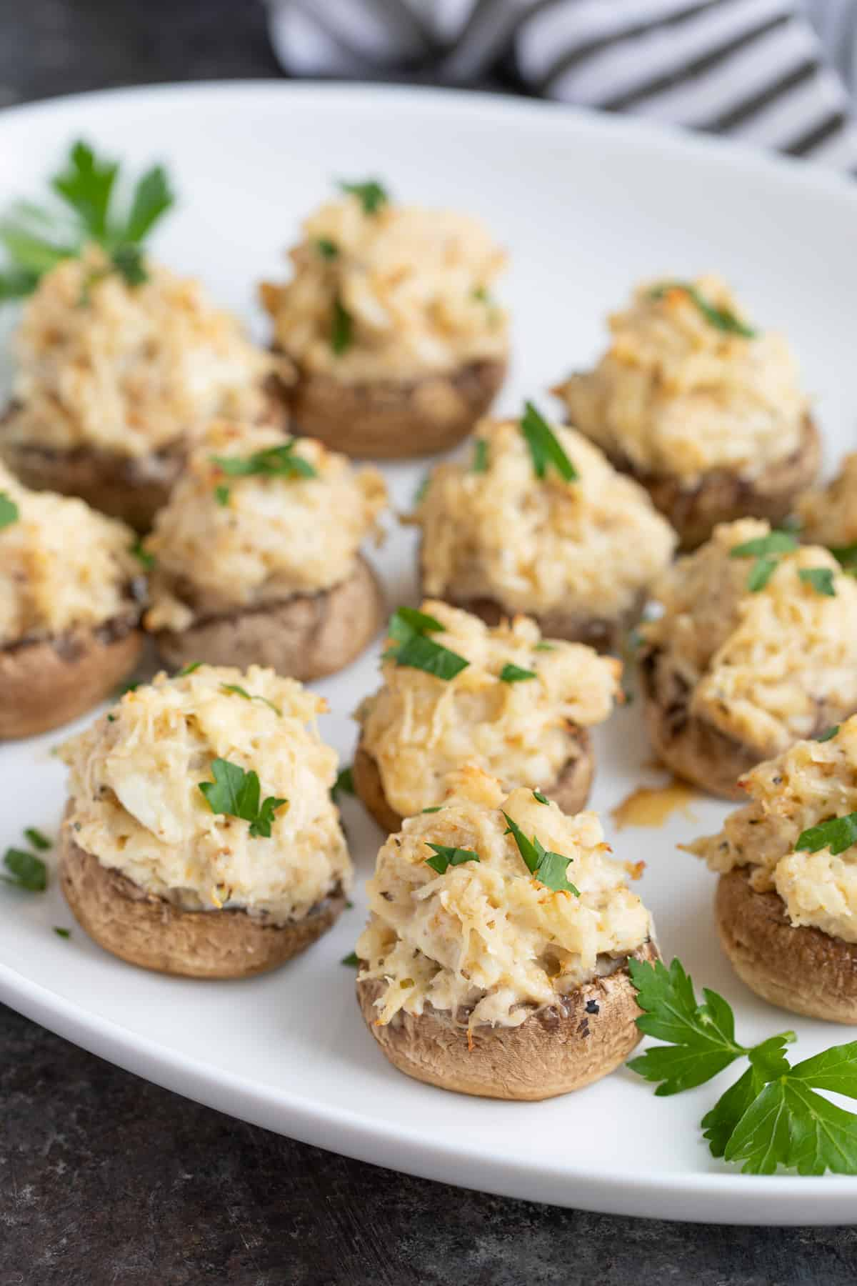 Closeup view of stuffed mushrooms on an oval white platter.