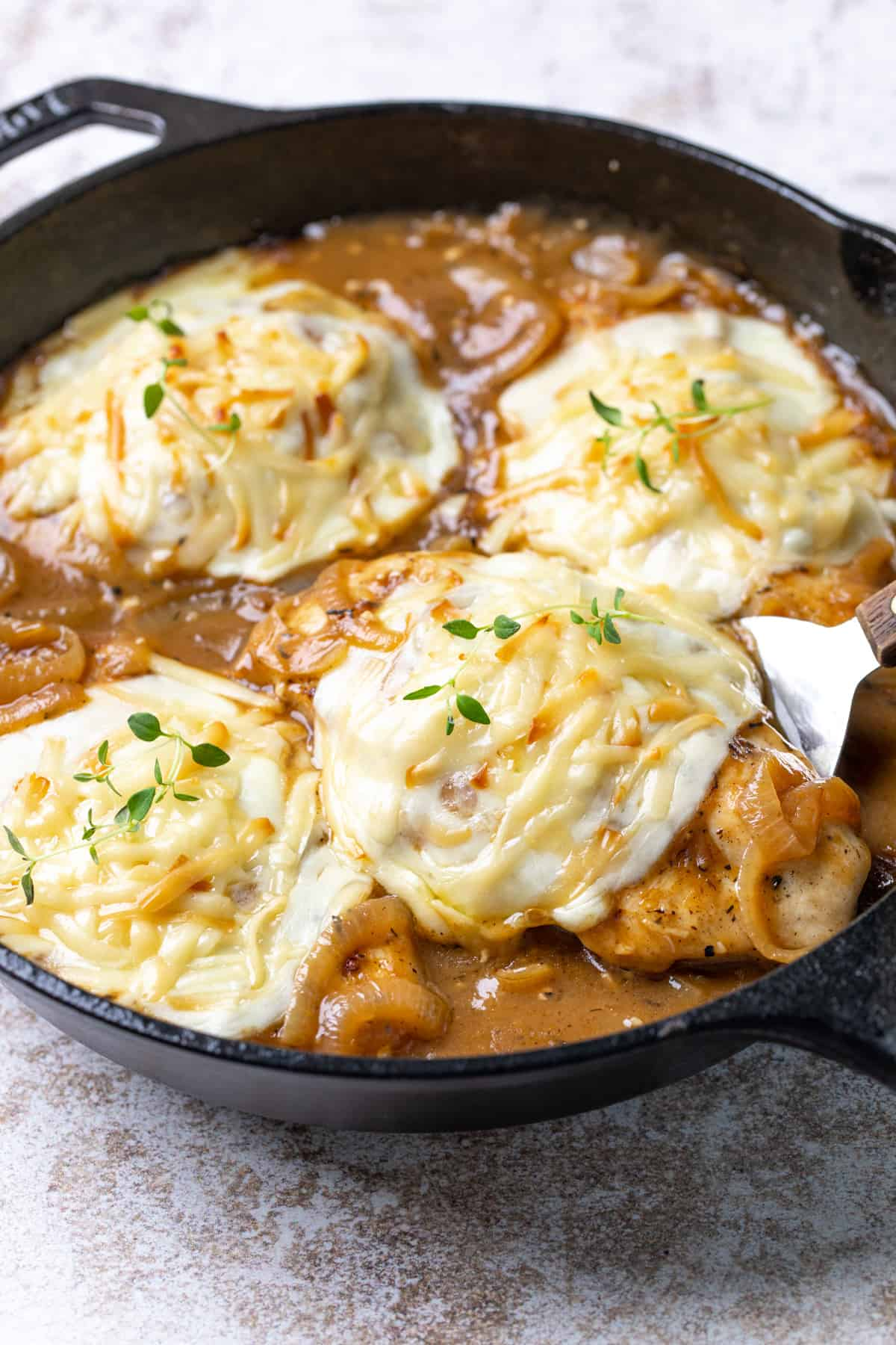 Closeup of chicken breasts topped with cheese in an onion gravy in a cast iron skillet.