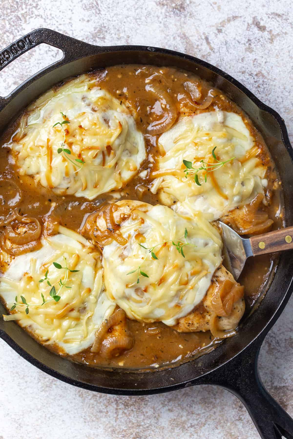 Overhead view of chicken topped with cheese in an onion gravy in a skillet.