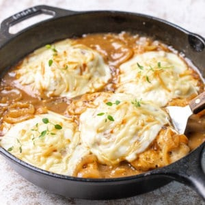 Closeup of French onion chicken in a cast iron skillet.