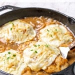 Closeup of French onion chicken in a cast iron skillet with overlay text.