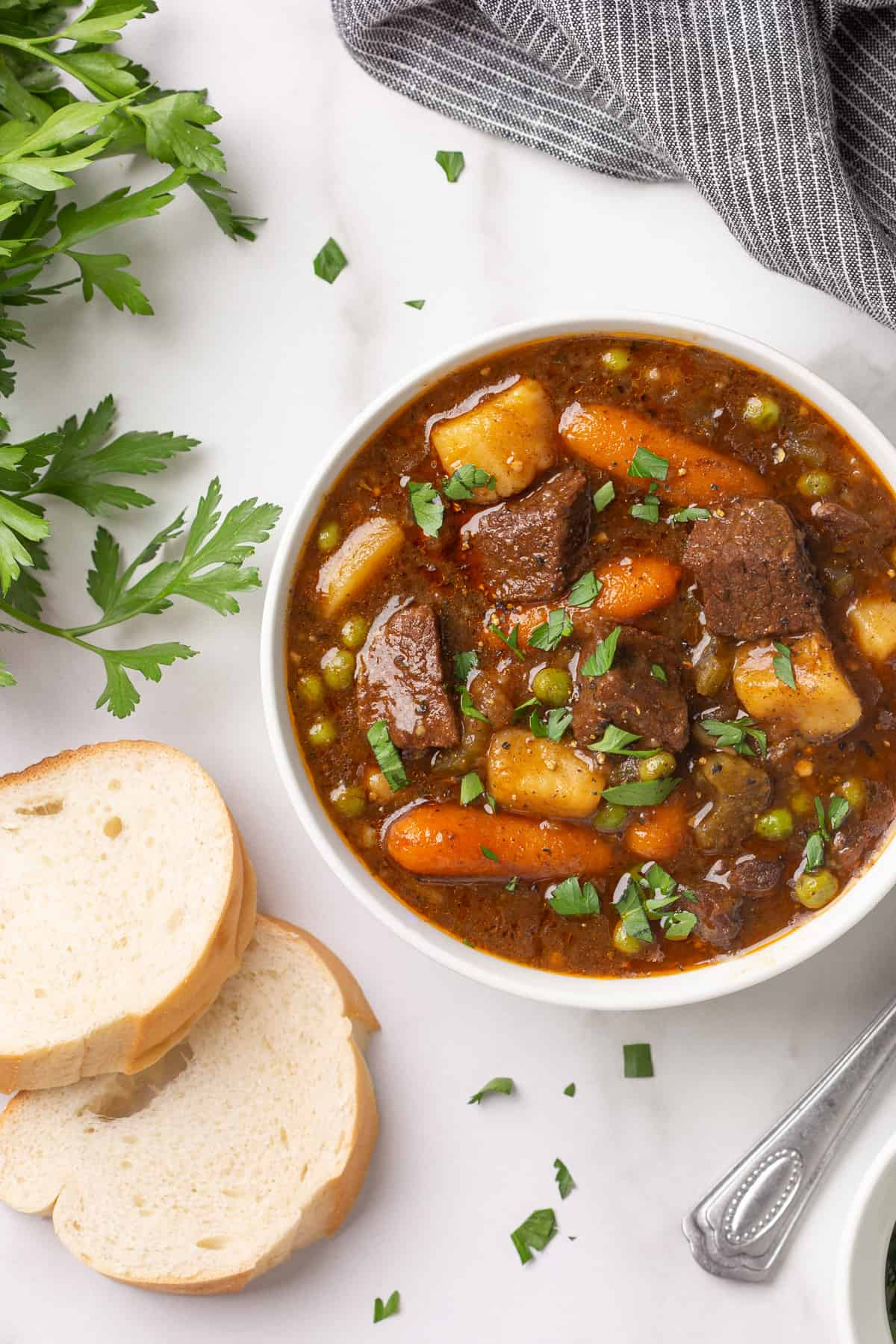 Overhead view of a white bowl of beef stew by sliced French bread.