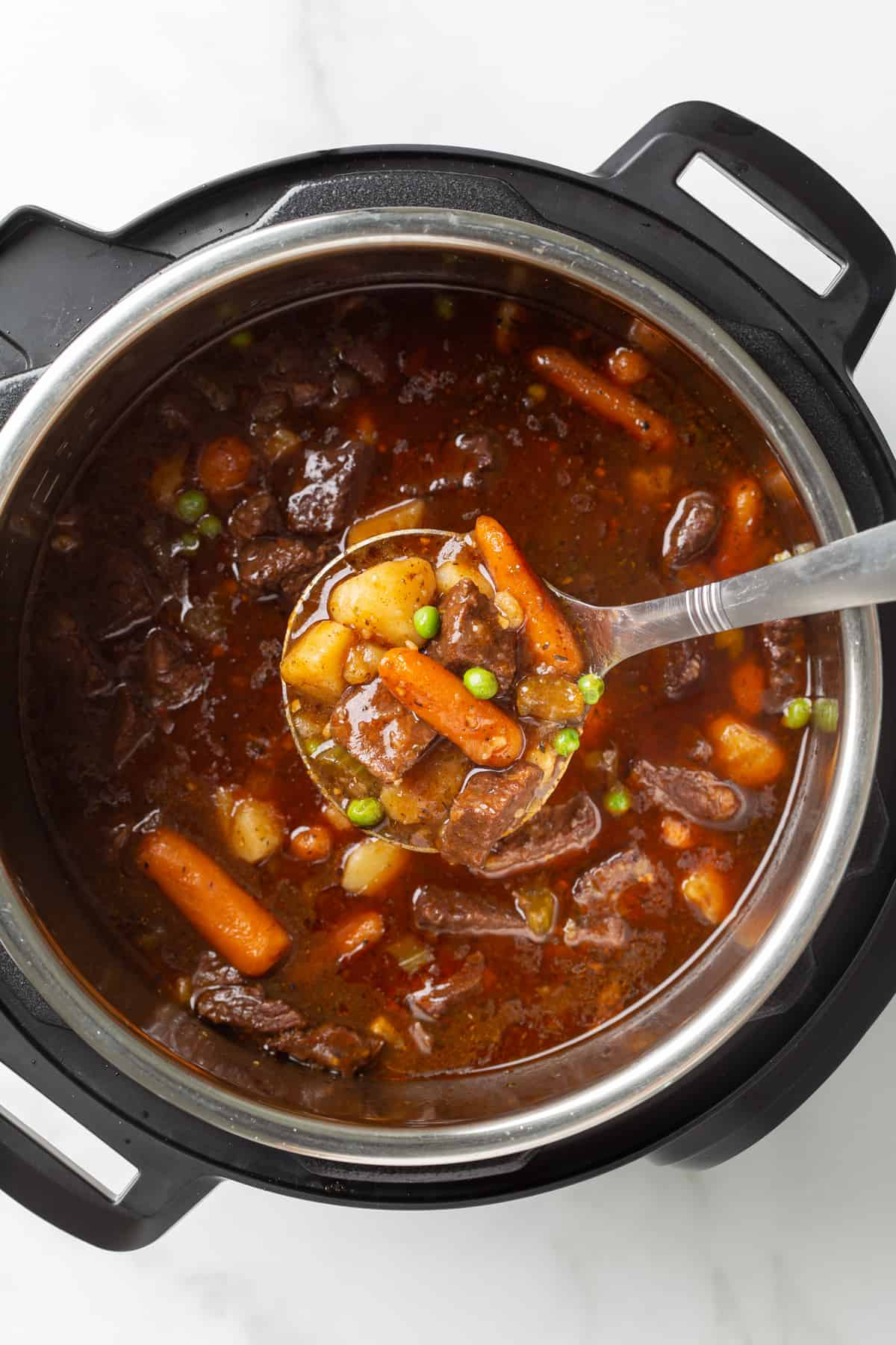 Overhead view of a stainless ladle ladling beef stew from an instant pot.