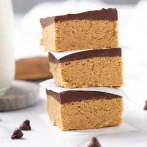 Closeup view of three stacked peanut butter bars. A glass of milk is in the background.