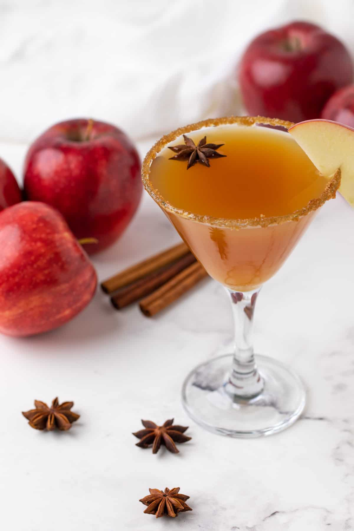 A martini with a caramel and brown sugar rim garnished with an apple slice and star anise.