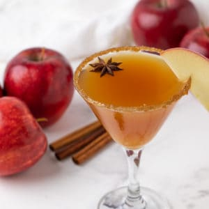 A martini with red apples and cinnamon sticks in the background.