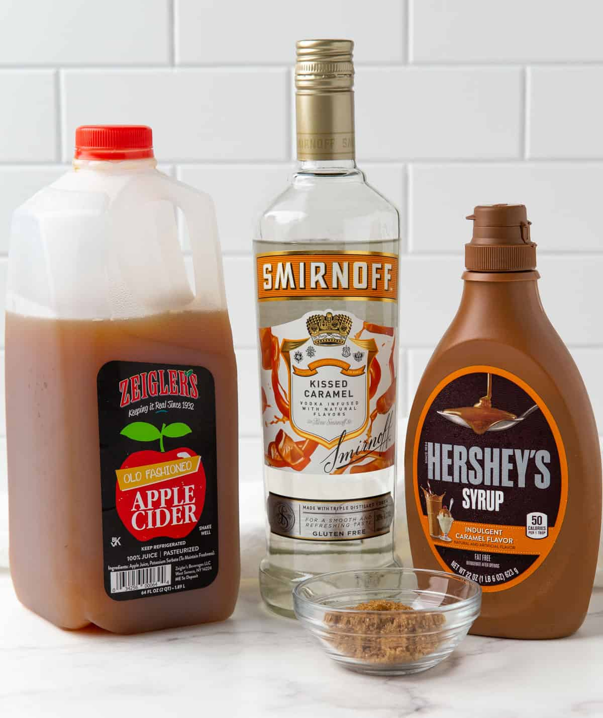 A jug of apple cider, bottle of caramel vodka, caramel syrup and brown sugar.