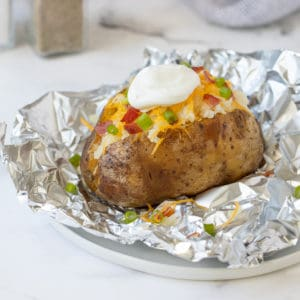 A slow cooked russet potato with toppings on top of a piece of aluminum foil.