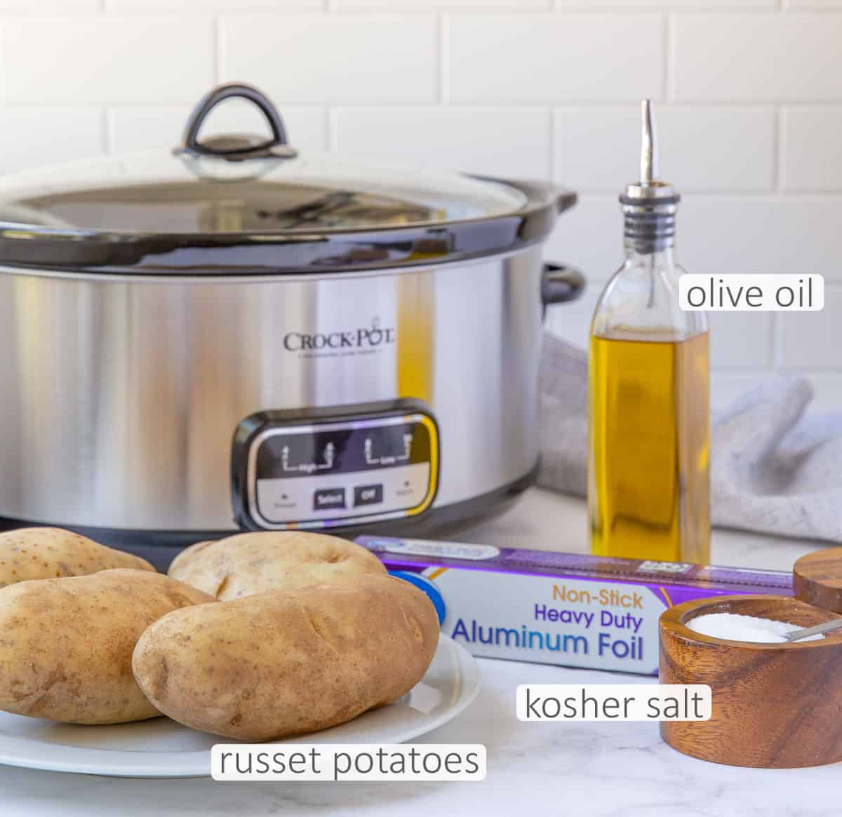 A slow cooker, russet potatoes, salt, olive oil and a roll of aluminum foil.