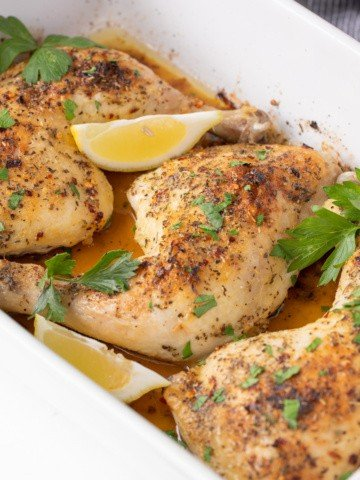 Three pieces of roasted dark meat chicken in a white baking dish.