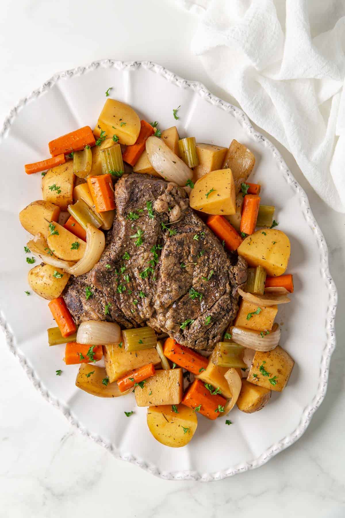 Overhead view of slow cooked beef chuck roast and vegetables on a white platter.