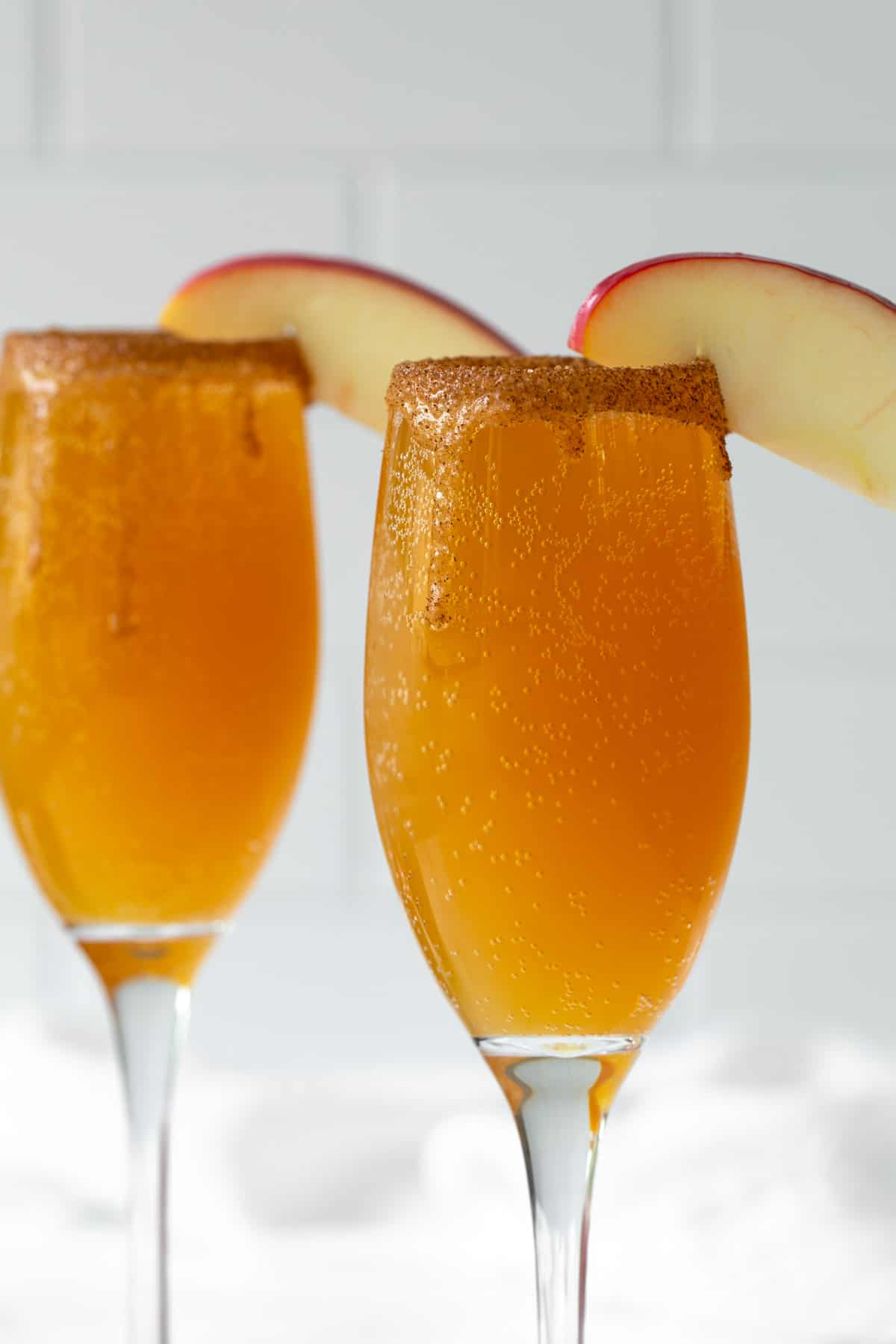 Closeup view of two caramel apple mimosas with a caramel and cinnamon sugar rim.