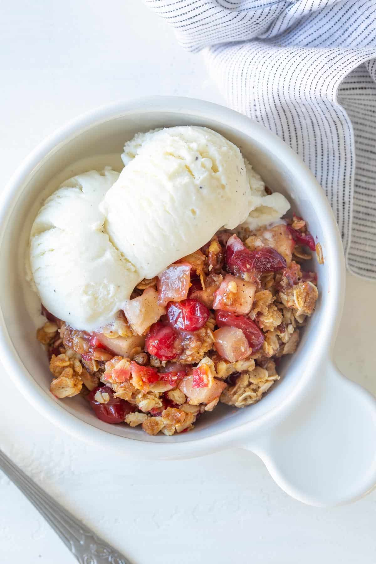 Overhead view of apple cranberry crisp in a white bowl with vanilla ice cream.
