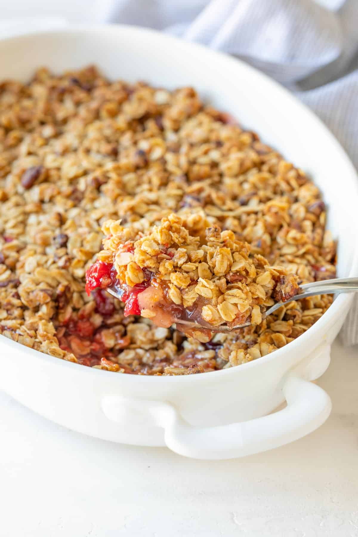 A closeup of a spoon removing cranberry apple crisp from a white baking dish.