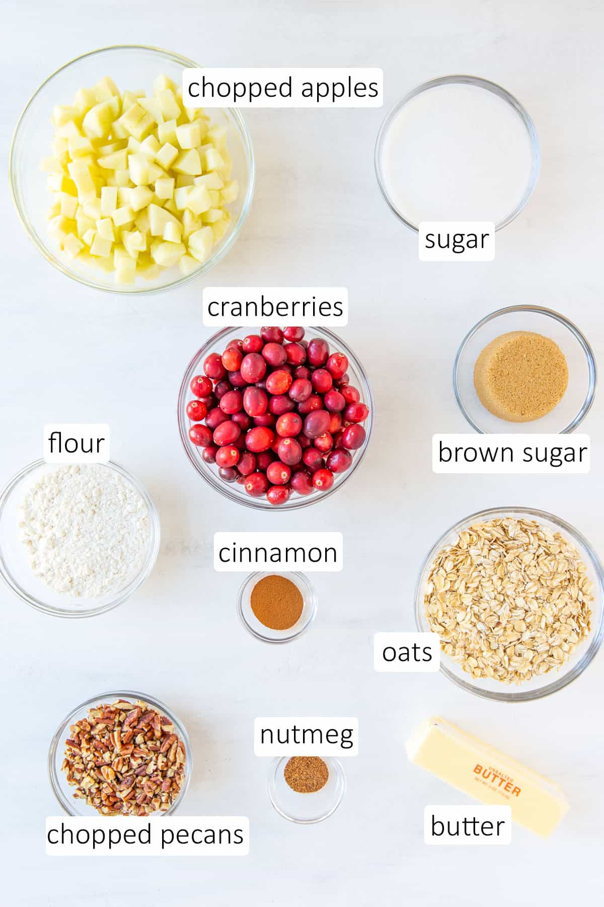 Overhead view of ingredients for cranberry apple crisp on a white surface.