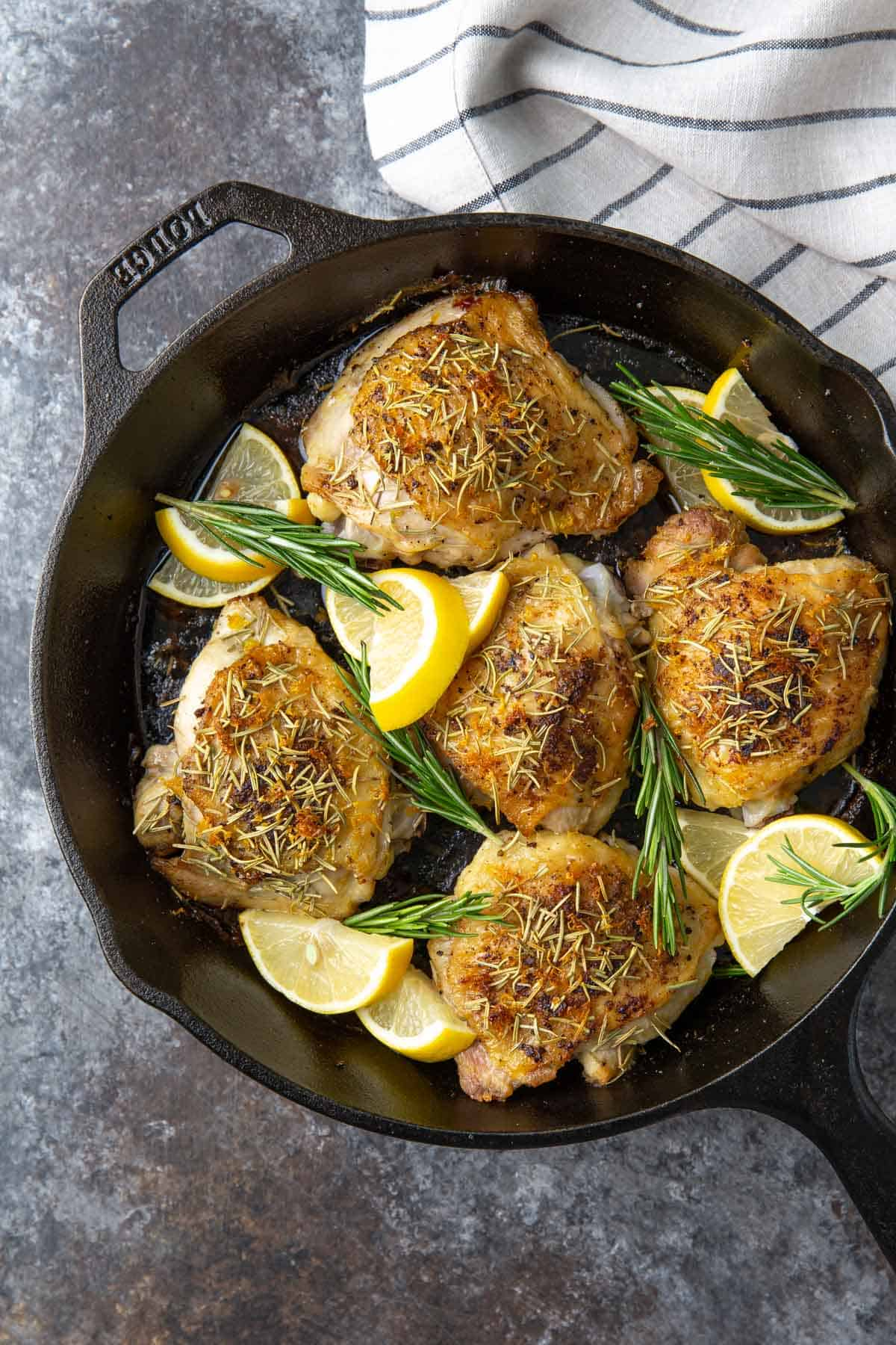 Overhead view of baked lemon rosemary chicken in a cast iron skillet.