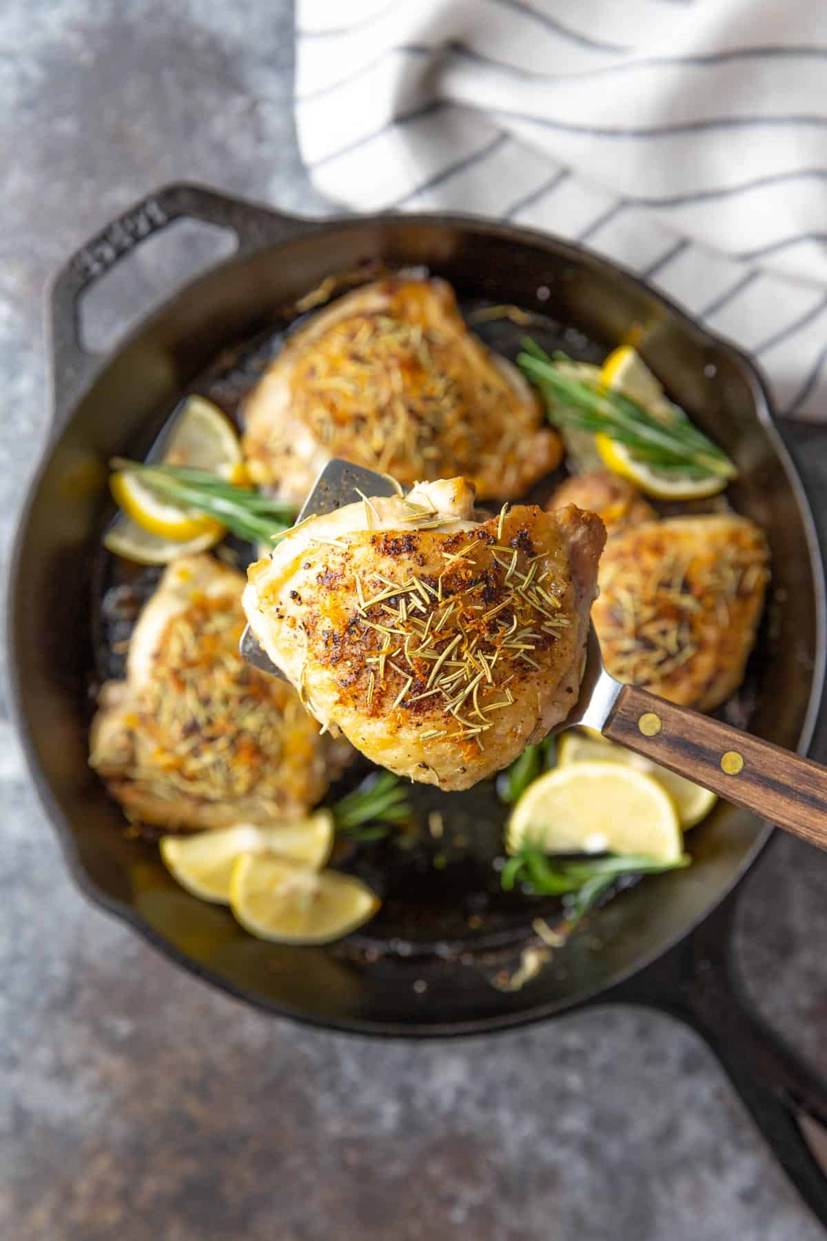 Overhead view of a spatula holding up a roasted chicken thigh over a skillet.