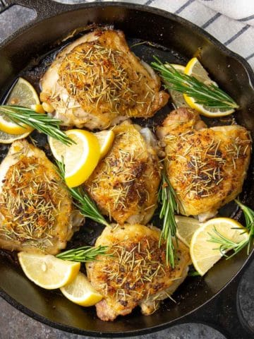 Overhead closeup of lemon rosemary chicken thighs in a skillet.