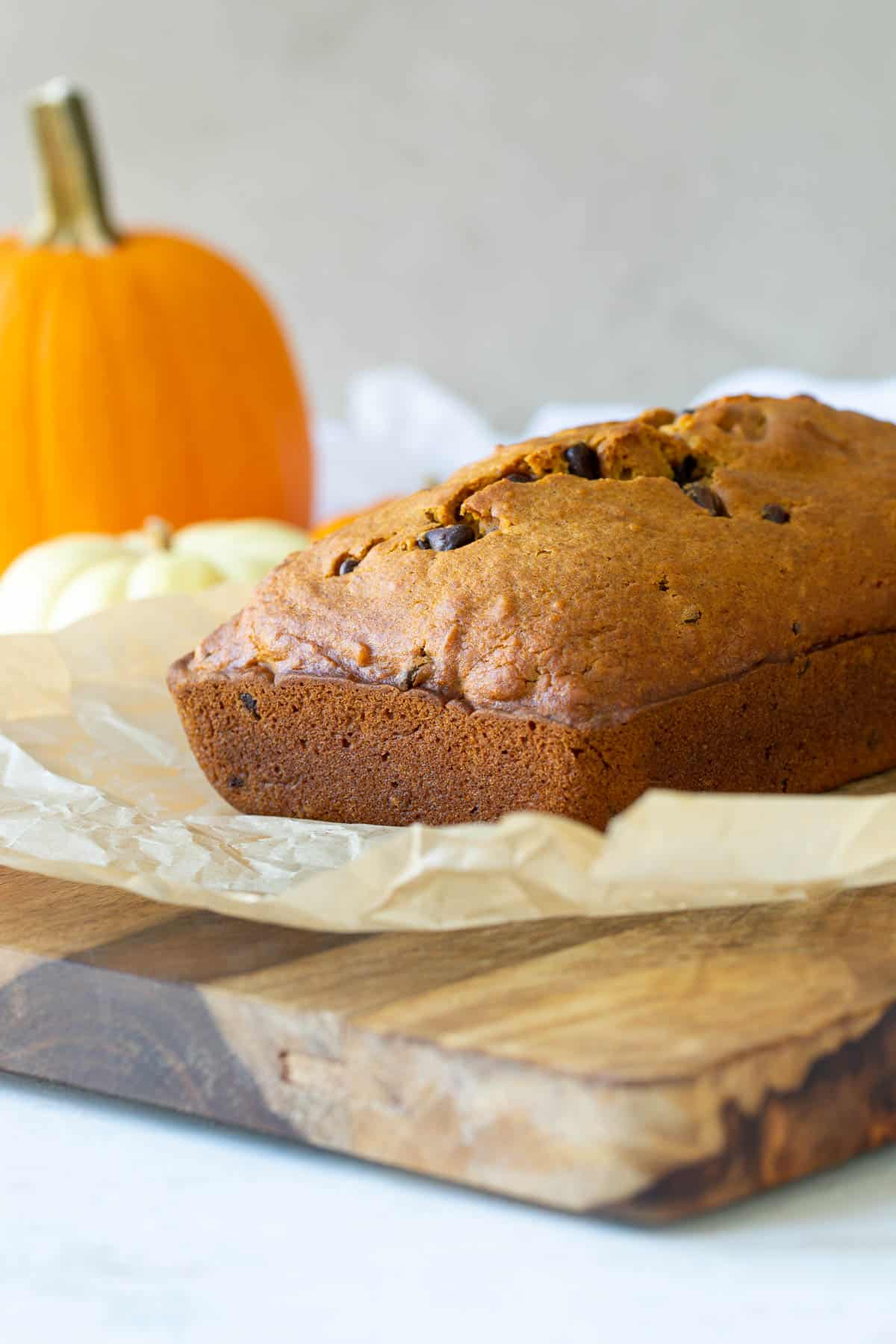 Front view of a loaf of pumpkin chocolate chip bread on a wood cutting board.