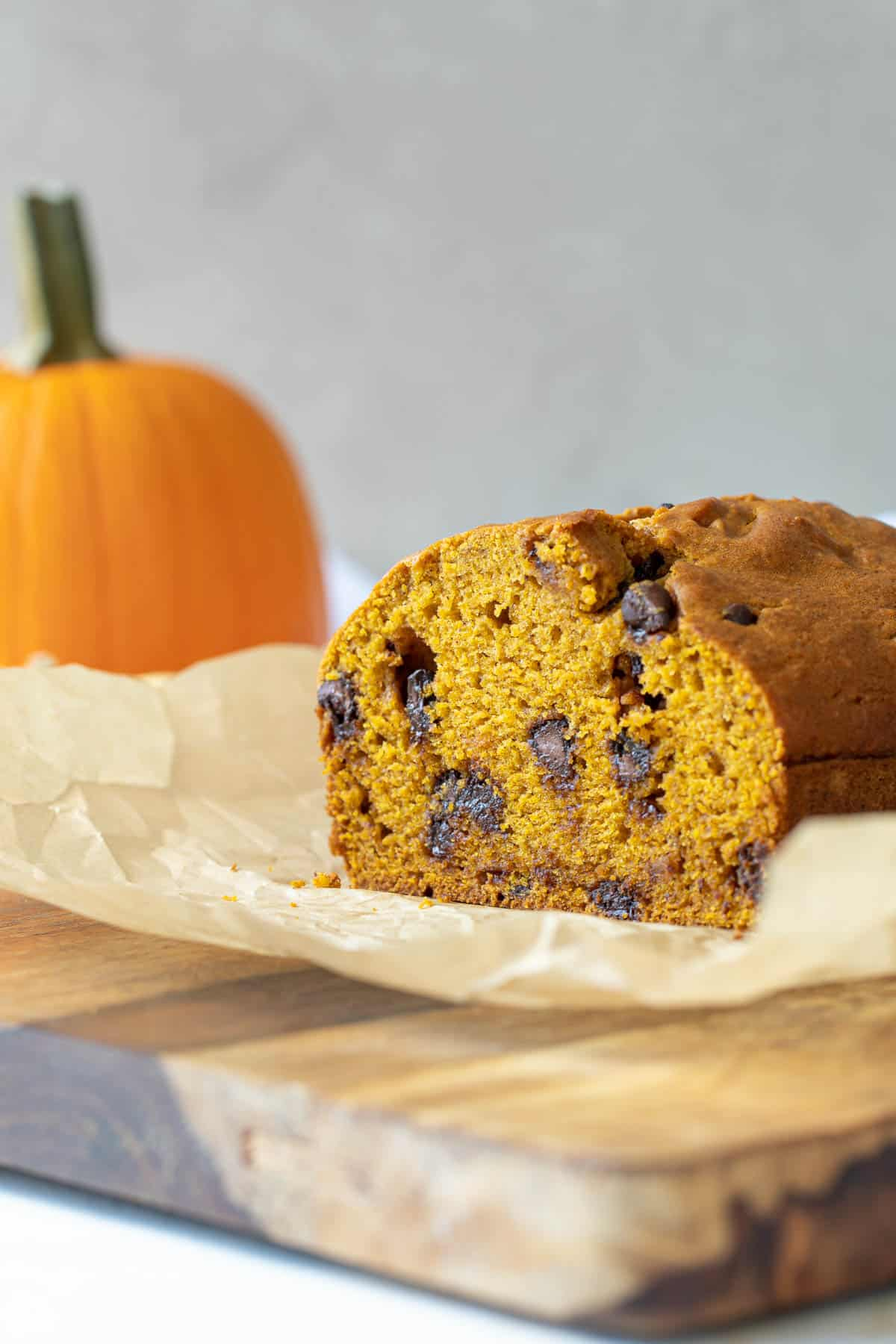 Front closeup view of a loaf of pumpkin chocolate chip bread on a cutting board.